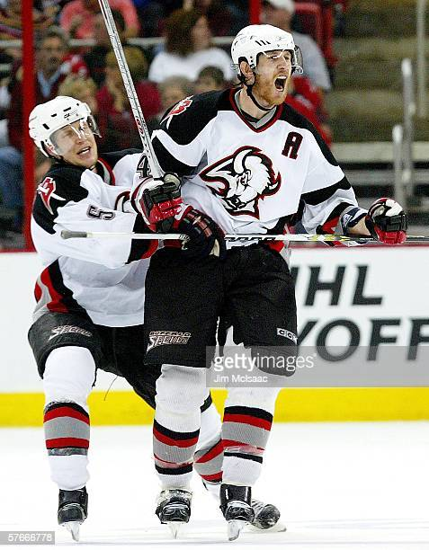 Jay McKee of the Buffalo Sabres celebrates his third period goal against the Carolina Hurricanes with teammate Toni Lydman in game one of the Eastern...