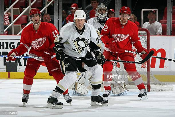 Jay Mckee of the Pittsburgh Penguins defends the net while Patrick Eaves and Mattias Ritola of the Detroit Red Wings wait for the puck during a NHL...