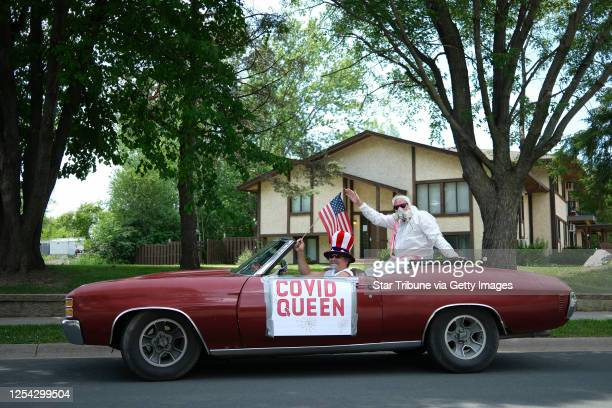 Jay Meyer, left, waved a US flag as Dave Roelike waved as they posed for a portrait on Laredo Drive in Chanhassen Saturday. Despite the city's...