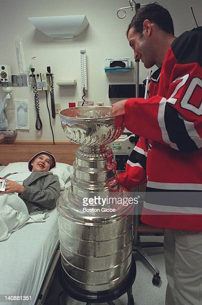 Jay Pandolfo a native of Burlington and a left winger for the NJ Devils shows 14yearold Megan Williams the Stanley Cup on his visit to the hospital