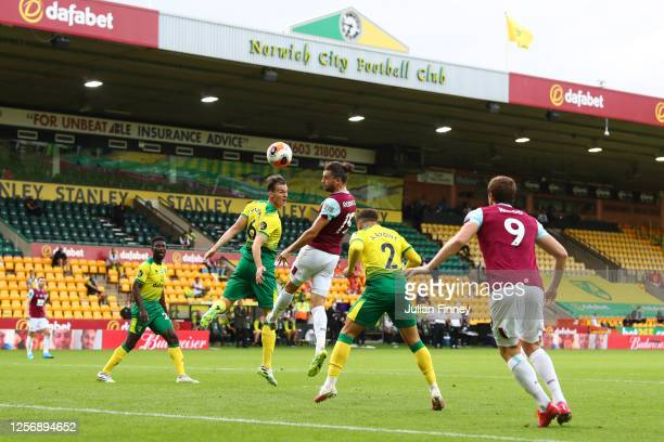 Jay Rodriguez of Burnley shoots a header under pressure from Christoph Zimmermann of Norwich City during the Premier League match between Norwich...