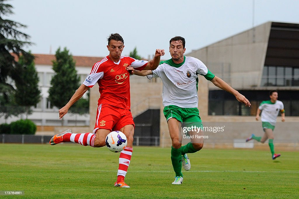 Jay Rodriguez of Southampton duels for the ball with Baron of UE Llagostera during a friendly match between Southampton FC and UE Llagostera at the Josep Pla i Arbones Stadium on July 17, 2013 in Girona, Spain.
