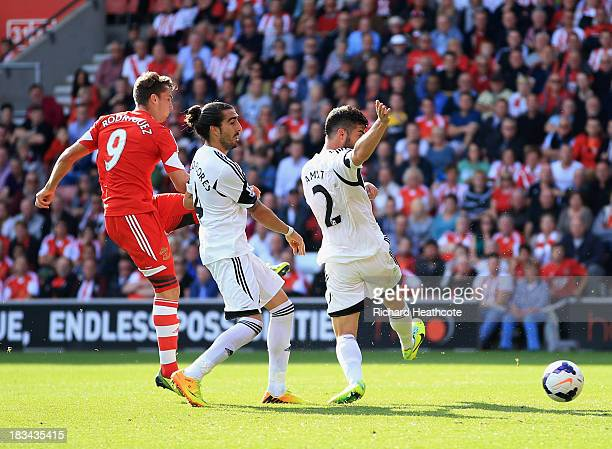 Jay Rodriguez of Southampton shoots past Chico Flores and Jordi Amat of Swansea City to score their second goal during the Barclays Premier League...