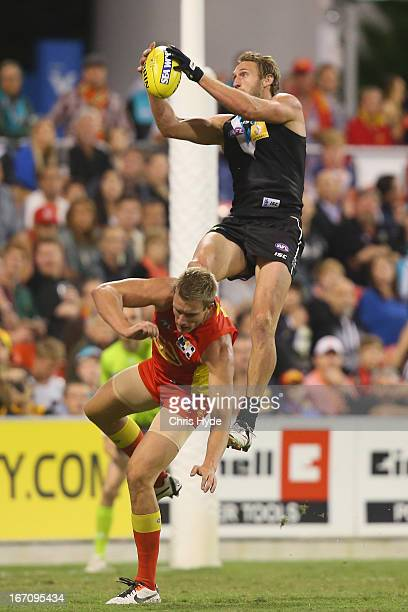 Jay Schultz of the Power takes a mark over Sam Day of the Suns during the round four AFL match between the Gold Coast Suns and Port Adelaide Power at...