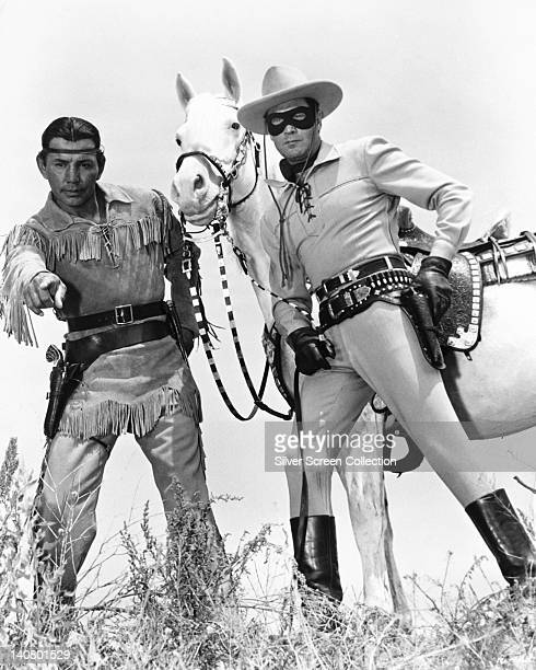 Jay Silverheels Canadian Mohawk actor and Clayton Moore US actor both in costume alongside 'Silver' the Lone Ranger's horse in a publicity still...