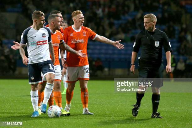 Jay Spearing and Callum Guy of Blackpool FC argue with referee John Busby during the Sky Bet Leauge One match between Bolton Wanderers and Blackpool...