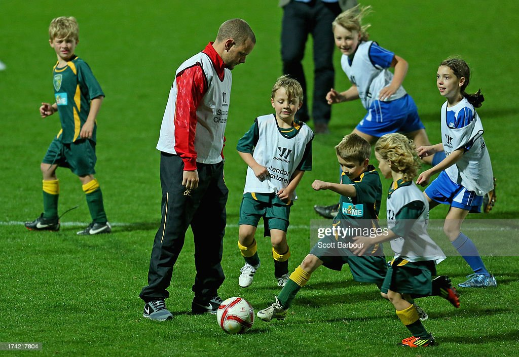 Jay Spearing of Liverpool kicks the ball as he plays against children during a football clinic at Lakeside Stadium on July 22, 2013 in Melbourne, Australia.