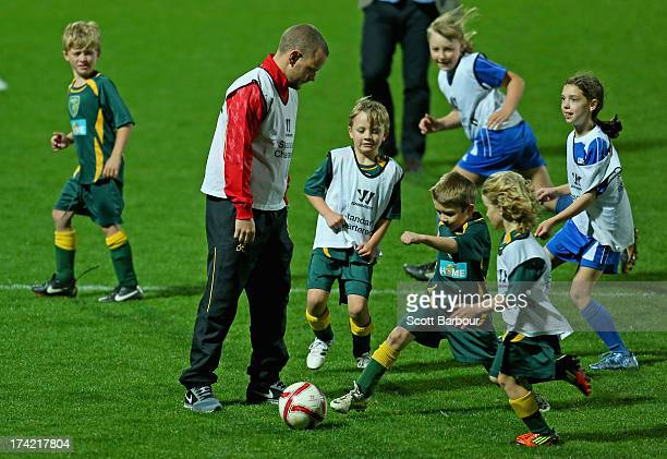 Jay Spearing of Liverpool kicks the ball as he plays against children during a football clinic at Lakeside Stadium on July 22 2013 in Melbourne...