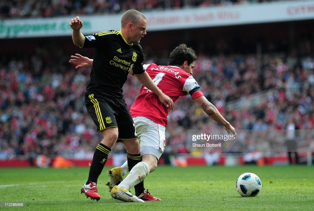 Jay Spearing of Liverpool tackles Cesc Fabregas of Arsenal and gives away a penalty kick during the Barclays Premier League match between Arsenal and Liverpool at the Emirates Stadium on April 17, 2011 in London, England.