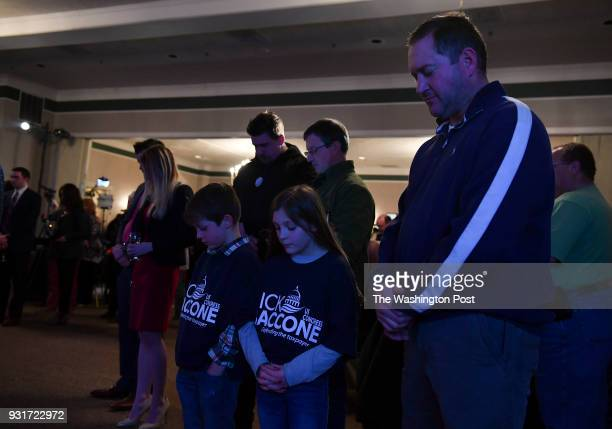 Jay Springer of Hunker Pa with his kids Tyten left and Lowen center pray before the election night party for Rick Saccone in a special election for...