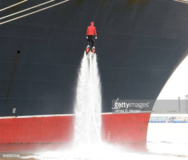 Jay St John flies close to Queen Mary 2 on July 05, 2015 in Liverpool, England. Champion flyboarder Jay St John donned a Cunard Bell Boy's uniform to...
