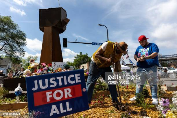 Jay Webb gardener for George Floyd Square and Damik Wright , brother of Daunte Wright who was shot and killed by a police officer, plant flowers in a...