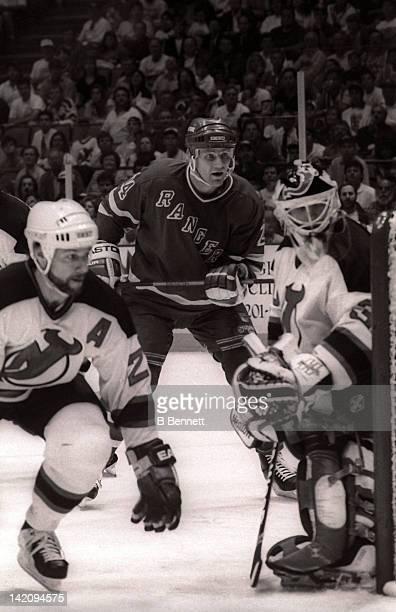 Jay Wells of the New York Rangers waits for the puck as Bruce Driver and goalie Martin Brodeur of the New Jersey Devils defend the net during Game 6...