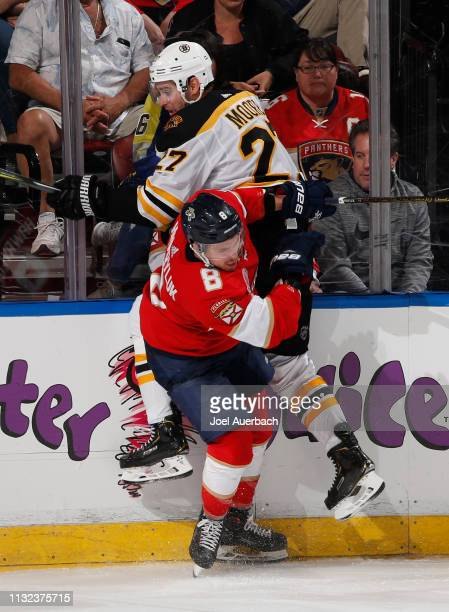 Jayce Hawryluk of the Florida Panthers checks John Moore of the Boston Bruins during third period action at the BBT Center on March 23 2019 in...