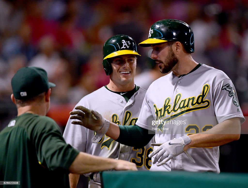 Jaycob Brugman #38 and Matt Joyce #23 of the Oakland Athletics smile as they come into the dugout, after scoring on a two run double from Khris Davis #2, to take a 5-2 lead over the Los Angeles Angels during the fifth inning at Angel Stadium of Anaheim on August 4, 2017 in Anaheim, California.