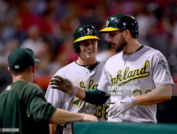 Jaycob Brugman and Matt Joyce of the Oakland Athletics smile as they come into the dugout after scoring on a two run double from Khris Davis to take...
