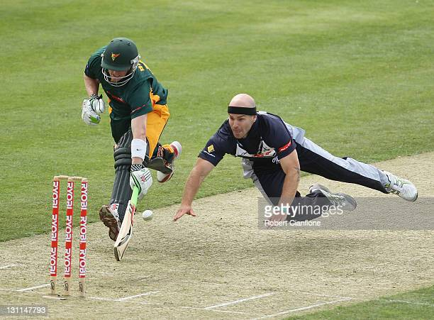 Jayde Herrick of the Bushrangers dives in an attempt to dismiss George Bailey of the Tigers during the Ryobi One Day Cup match between the Tasmania...