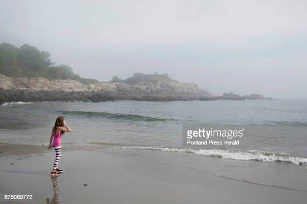 Jayden Baker walks up the water's edge during a humid and foggy morning at Fort Williams Park Baker is vacationing in Maine with her family from...