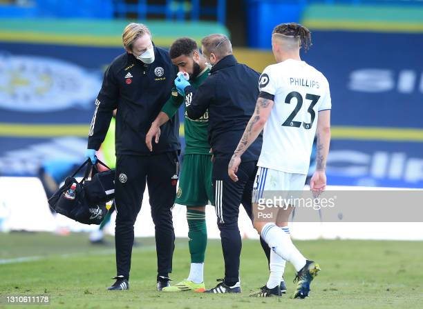Jayden Bogle of Sheffield United holds his nose as he goes off injured during the Premier League match between Leeds United and Sheffield United at...