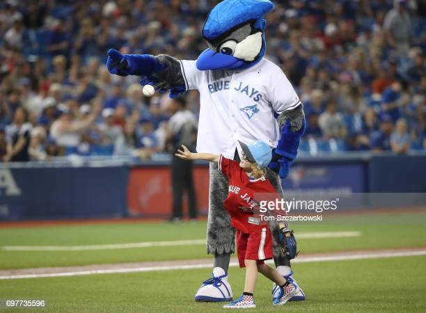 Jayden Grilli the son of Jason Grilli of the Toronto Blue Jays throws out the first pitch on Fathers Day as Ace the mascot watches before the start...