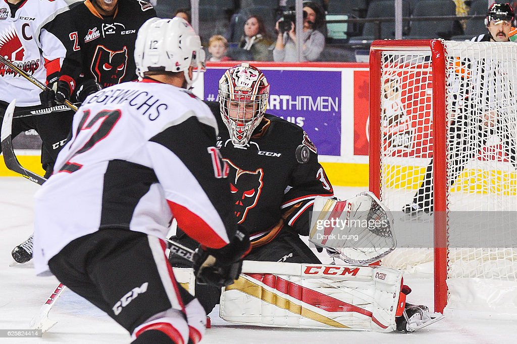 Jayden Halbgewachs #12 of the Moose Jaw Warriors shoots the puck past Cody Porter #31 of the Calgary Hitmen during a WHL game at Scotiabank Saddledome on November 25, 2016 in Calgary, Alberta, Canada.