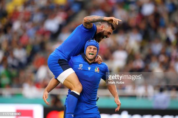 Jayden Hayward of Italy jumps on top of teammate Dean Budd as they celebrate their team's second try during the Rugby World Cup 2019 Group B game...
