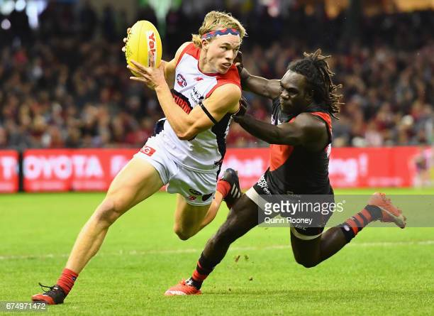 Jayden Hunt of the Demons breaks free of a tackle by Anthony McDonaldTipungwuti of the Bombers during the round six AFL match between the Essendon...