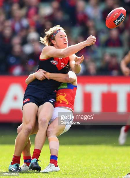 Jayden Hunt of the Demons handballs whilst being tackled by Dayne Zorko of the Lions during the round 22 AFL match between the Melbourne Demons and...