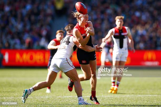 Jayden Hunt of the Demons handpasses the ball whilst being tackled by Maverick Weller of the Saints during the round 21 AFL match between the...