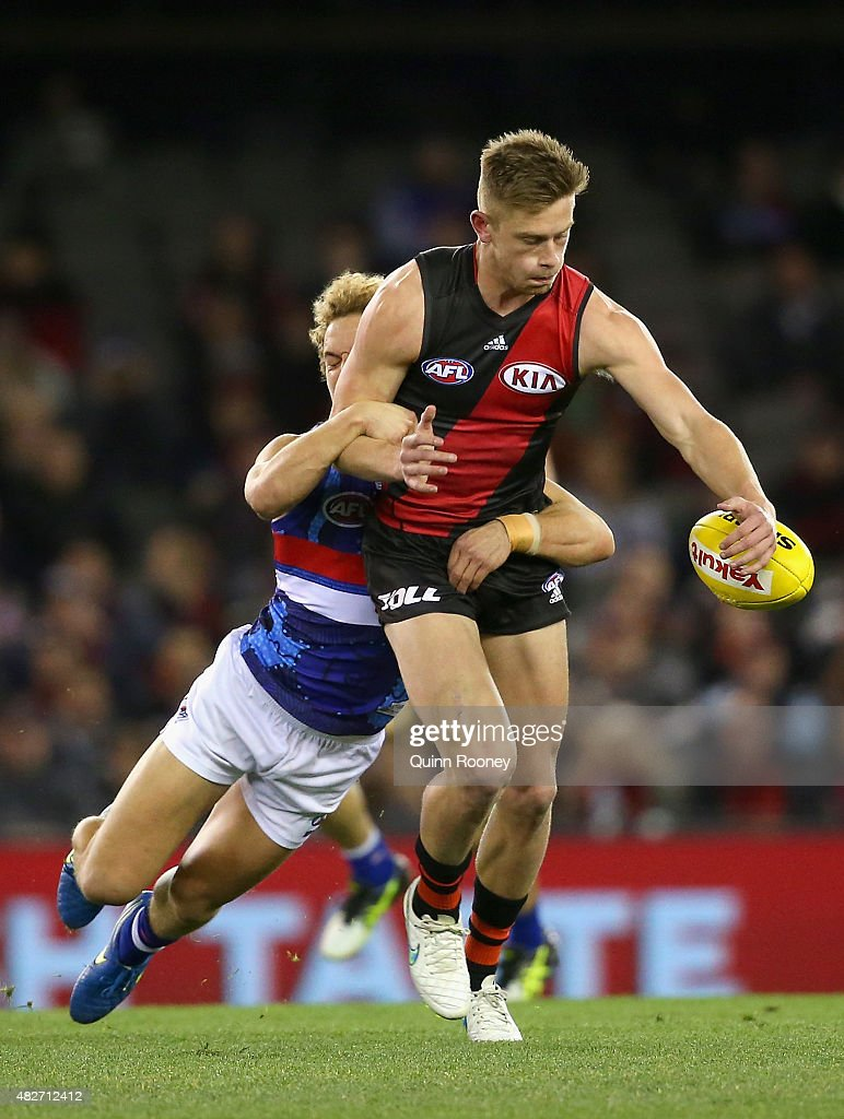 Jayden Laverde of the Bombers kicks whilst being tackled by Mitch Wallis of the Bulldogs during the round 18 AFL match between the Essendon Bombers and the Western Bulldogs at Etihad Stadium on August 2, 2015 in Melbourne, Australia.