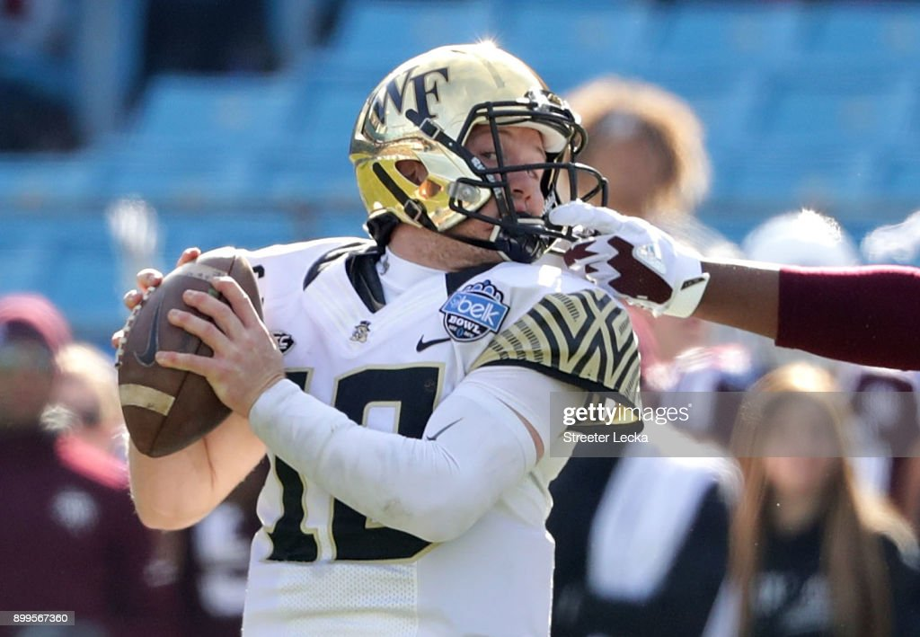 Jayden Peevy #93 of the Texas A&M Aggies grabs the facemask of John Wolford #10 of the Wake Forest Demon Deacons during the Belk Bowl at Bank of America Stadium on December 29, 2017 in Charlotte, North Carolina.