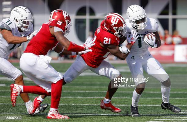 Jayden Reed of the Michigan State Spartans runs the ball against Noah Pierre of the Indiana Hoosiers during the game at Indiana University on October...