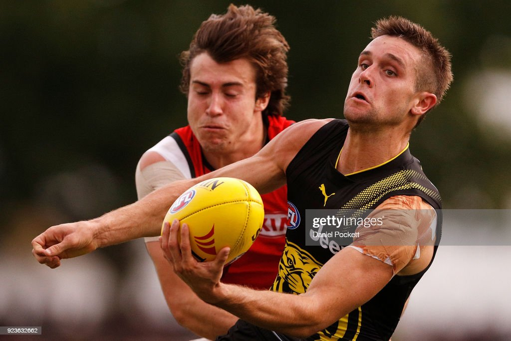 Jayden Short of the Tigers handpasses the ball whilst being tackled by Andrew McGrath of the Bombers during the JLT Community Series AFL match between the Essendon Bombers and the Richmond Tigers at Norm Minns Oval on February 24, 2018 in Wangaratta, Australia.
