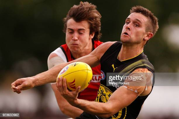 Jayden Short of the Tigers handpasses the ball whilst being tackled by Andrew McGrath of the Bombers during the JLT Community Series AFL match...