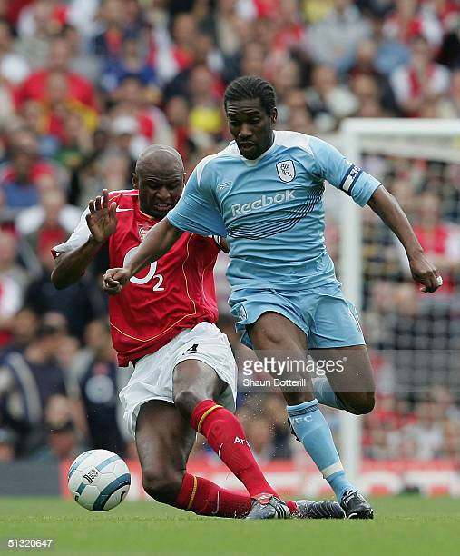 Jay-Jay Okocha of Bolton Wanderers battles for the ball with Patrick Vieira of Arsenal during the Barclays Premiership match between Arsenal and...
