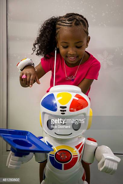 Jayla aged 4 plays with an 'Emiglio' robot in Hamley's toy shop on June 26 2014 in London England The remote controlled robot which retails for 125...