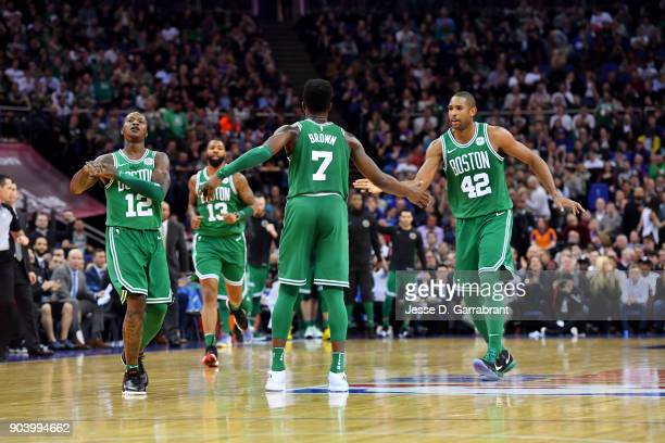 Jaylen Brown exchanges high fives with teammates Terry Rozier and Al Horford of the Boston Celtics during the game against the Philadelphia 76ers on...