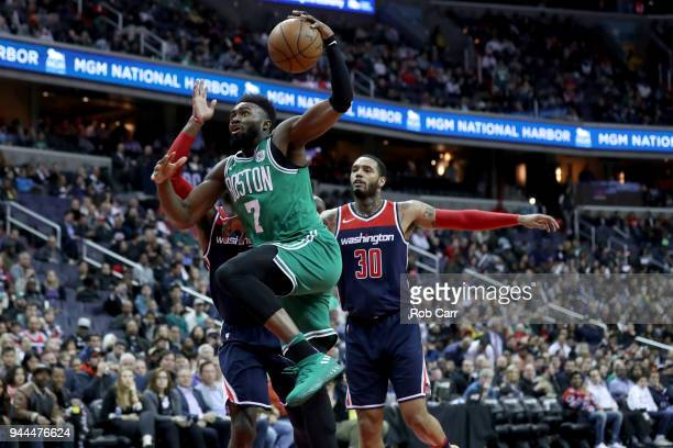 Jaylen Brown of the Boston Celtics drives the basket against John Wall of the Washington Wizards and Mike Scott in the second half at Capital One...