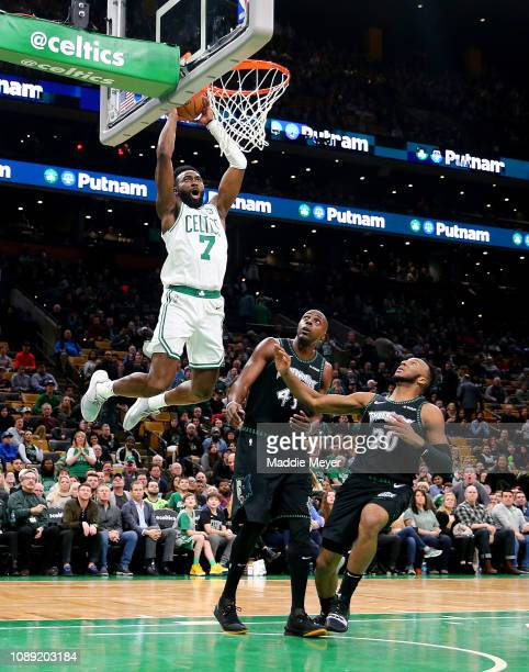Jaylen Brown of the Boston Celtics dunks over Anthony Tolliver of the Minnesota Timberwolves and Josh Okogie during the fourth quarter at TD Garden...