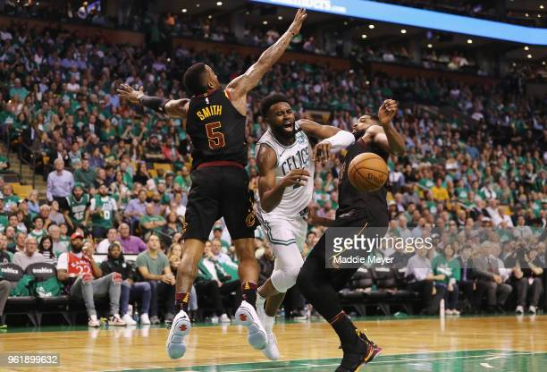 Jaylen Brown of the Boston Celtics loses the ball as he drives to the basket against JR Smith and Tristan Thompson of the Cleveland Cavaliers in the...
