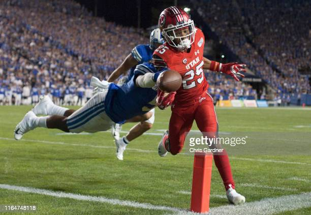 Jaylen Dixon of the Utah Utes gets the ball into the end zone for a touchdown as Dayan Ghanwoloku of the BYU Cougars tries to strip the ball during...