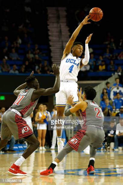 Jaylen Hands of the UCLA Bruins passes the ball as Both Gach of the Utah Utes and Sedrick Barefield of the Utah Utes attempt to block during the...