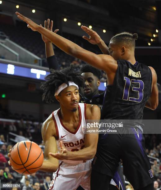 Jaylen Nowell and Hameir Wright of the Washington Huskies defend Elijah Stewart of the USC Trojans under the basket in the first half of the game at...