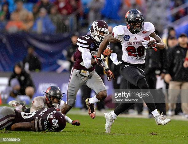 Jaylen Samuels of the North Carolina State Wolfpack breaks away from Taveze Calhoun of the Mississippi State Bulldogs for a touchdown during the Belk...