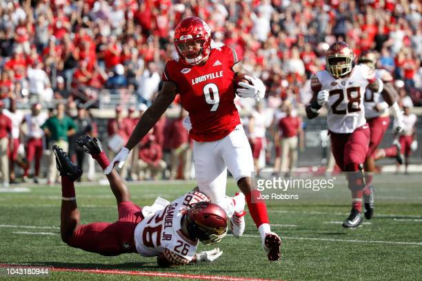 Jaylen Smith of the Louisville Cardinals tries to break a tackle after catching a pass against Asante Samuel Jr #26 of the Florida State Seminoles in...