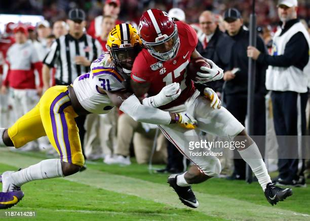 Jaylen Waddle of the Alabama Crimson Tide is tackled by Cameron Lewis of the LSU Tigers during the second half at Bryant-Denny Stadium on November 9,...