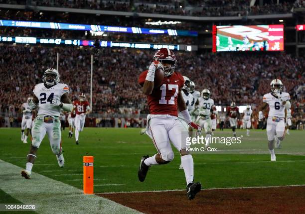 Jaylen Waddle of the Alabama Crimson Tide takes in this reception for a touchdown against the Auburn Tigers at BryantDenny Stadium on November 24...