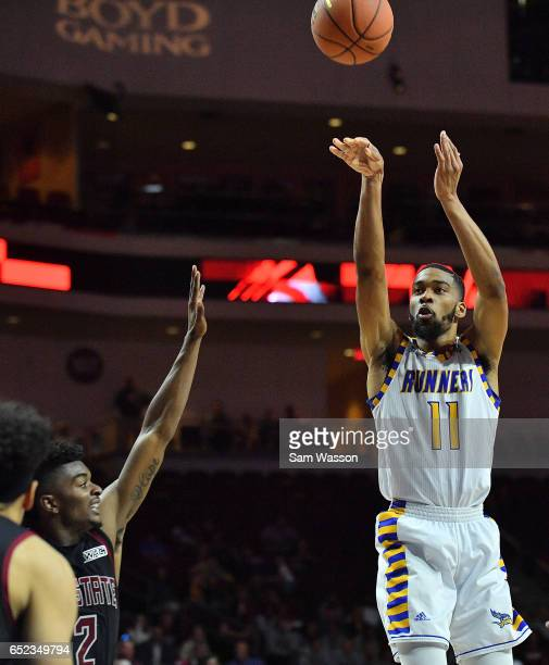 Jaylin Airington of the Cal State Bakersfield Roadrunners shoots against Braxton Huggins of the New Mexico State Aggies during the championship game...