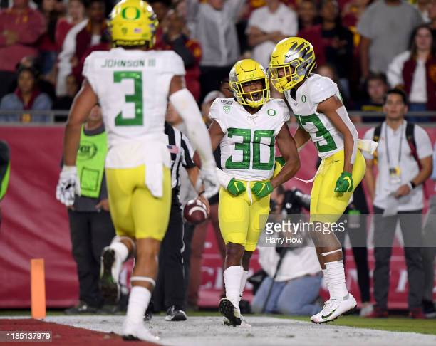 Jaylon Redd of the Oregon Ducks celebrates his touchdown run with Josh Delgado and Johnny Johnson III to take a 1410 lead over the USC Trojans during...