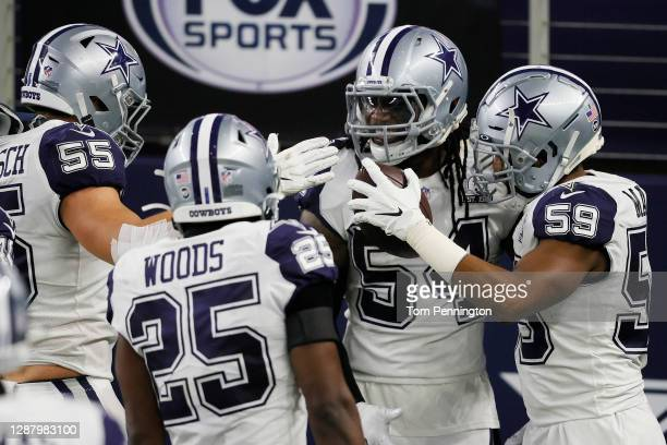 Jaylon Smith of the Dallas Cowboys celebrates his interception alongside Xavier Woods and Justin March during the third quarter of a game against the...